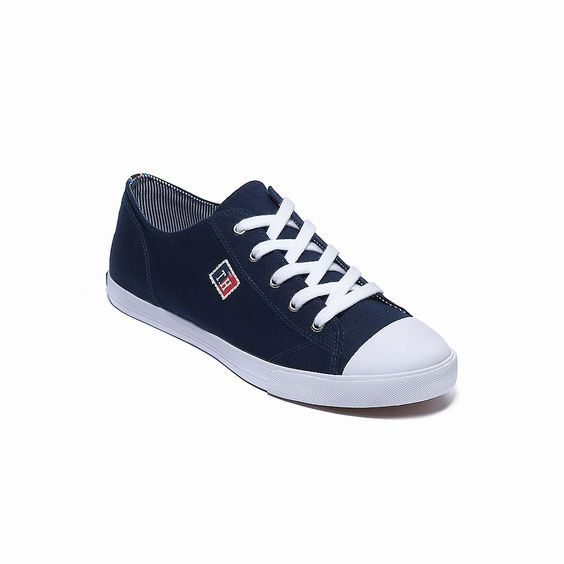 Tommy Hilfiger women's shoe. You can't get any more classic than this—the iconic tennis shoe, in the same silhouette you remember as a kid, and fresh details like ribbon trim and signature patch detail. • Cotton canvas upper and rubber sole.• Contrast lining, textured rubber sole, Hilfiger plaque at heel. • Imported.