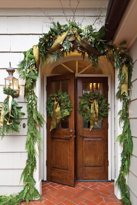 Beautiful Christmas decorations of evergreen garlands and wreaths on exterior doors