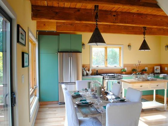 As seen on HGTV's Vacation House for Free...a large rustic dining table dressed in coastal decor sits in front of floor-to-ceiling windows and glass doors, offering an excellent view.