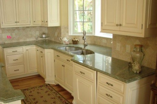 cream cabinets with backsplash and green marble countertop