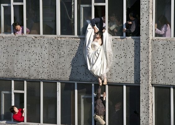 A distressed bride attempts suicide in China after her fiance abruptly called off their marriage. Still in her wedding gown, she tried to kill herself by jumping out of a window of a seventh floor building. Right as she jumped, a man managed to catch and save her.