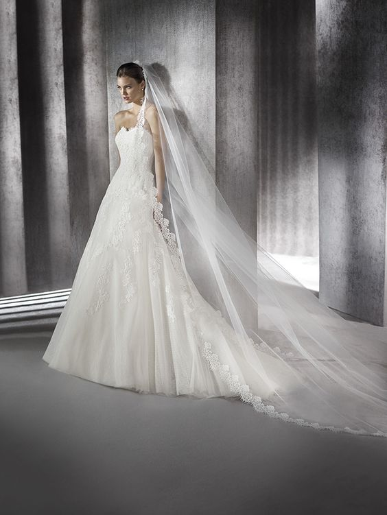 Wedding dress with long sleeves in petit pois tulle decorated with lace appliqués and thread embroidery. Sweetheart bodice with jacket with off-the-shoulder neckline and 3/4 sleeves in lace.