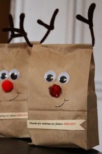 paper bags decorated as reindeer with red poms and pipe cleaners