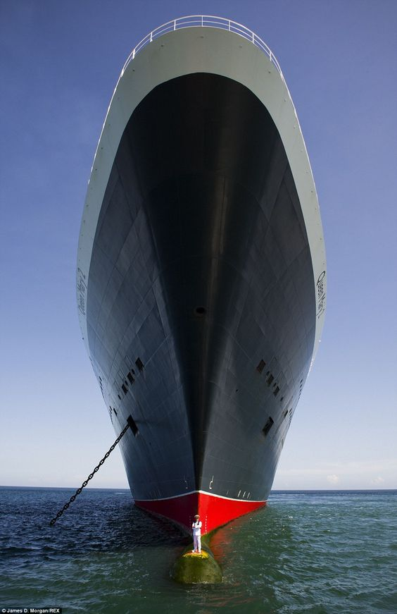 Captain Kevin Oprey stands on the bulbous bow of the Queen Mary 2 off the coast of Bali in photographs taken to mark the ocean liner's tenth anniversary in May