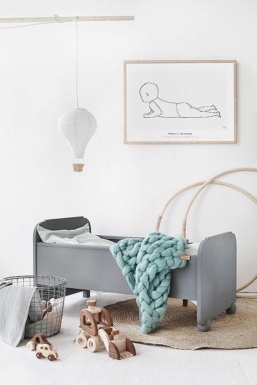 Chambre d'enfant aux couleurs pastel avec une suspension montgolfière au-dessus du lit