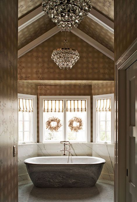 In the master bath, a chandelier spotlights a dramatic tub, made in Peru from a single piece of stone.