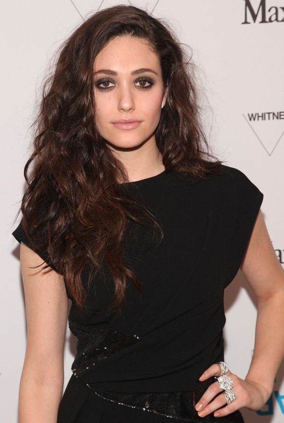 Pin for Later: 12 Stars Who Will Convince You to Wear Your Hair Naturally Curly Emmy Rossum Don't be afraid to pump up the volume! Use a dollop on damp hair and focus on concentrating the product at your roots to add height to your style.