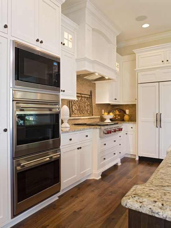 Double oven with microwave  along side with range top and understated range hood