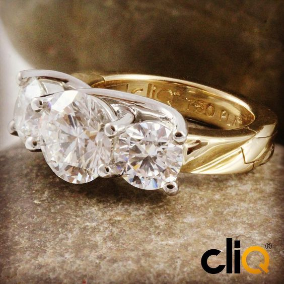 Three stone diamond ring in platinum and 18k gold with a carved shank featuring superfit technology