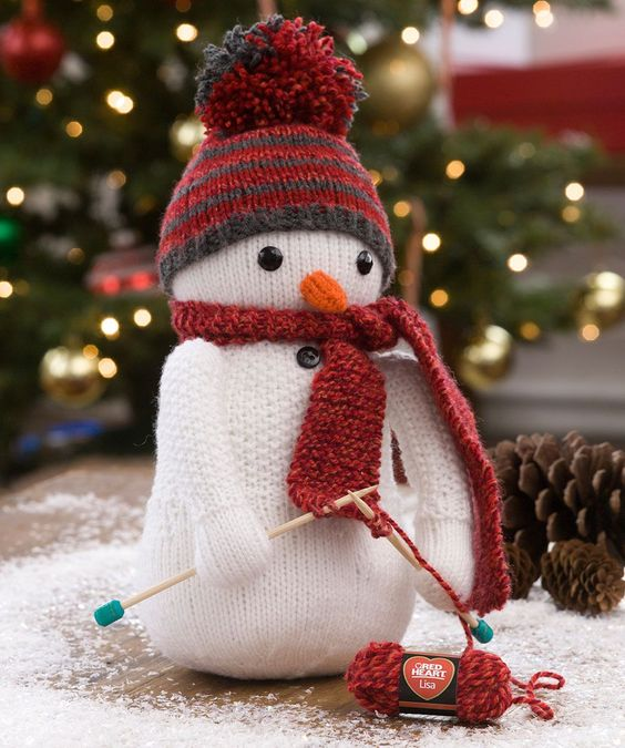 This friendly snowman is in the middle of knitting himself a scarf! He's already wearing a textured cardigan and hat he made. Instructions for making mini ball of Red Heart Lisa are included.