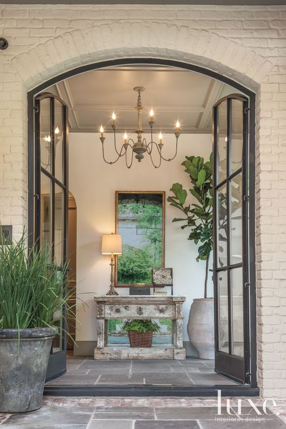 Architect Dillon Kyle used steel-framed glass doors from Hope's Windows to welcome guests into the home's soaring entry. The flooring, Pennsylvania green flagstone with a natural cleft finish, adds texture to the space, as does the ceiling detail. The antique chandelier, circa 1900, is from Skelton - St. John.