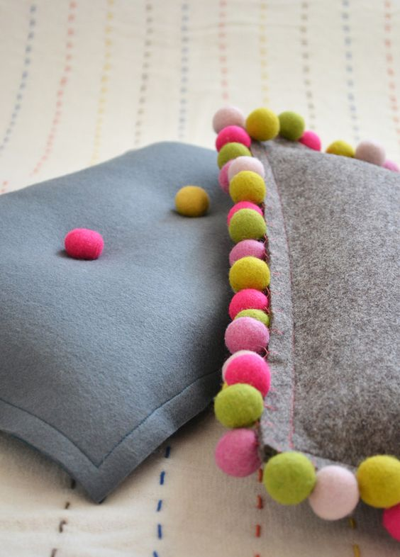 Handmade felt cushions with pompoms: