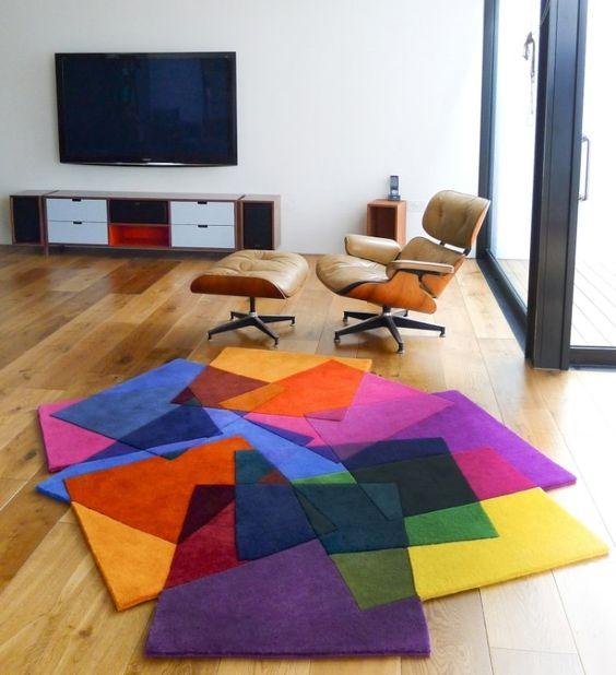 tapis multicolore, fauteuil relax en cuir beige et bois, parquet en bois et meuble TV bas en bois et blanc