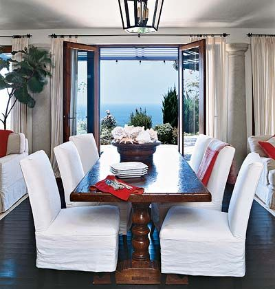 A large wooden dining room table with red linens and bright white ...