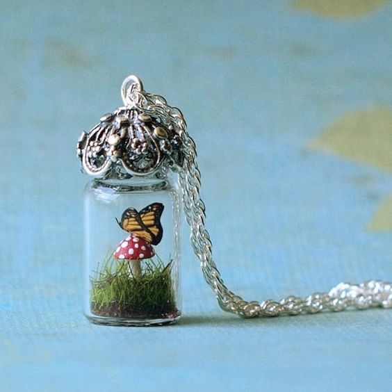 Tiny butterfly on mushroom inside tiny glass vial on a silver necklace
