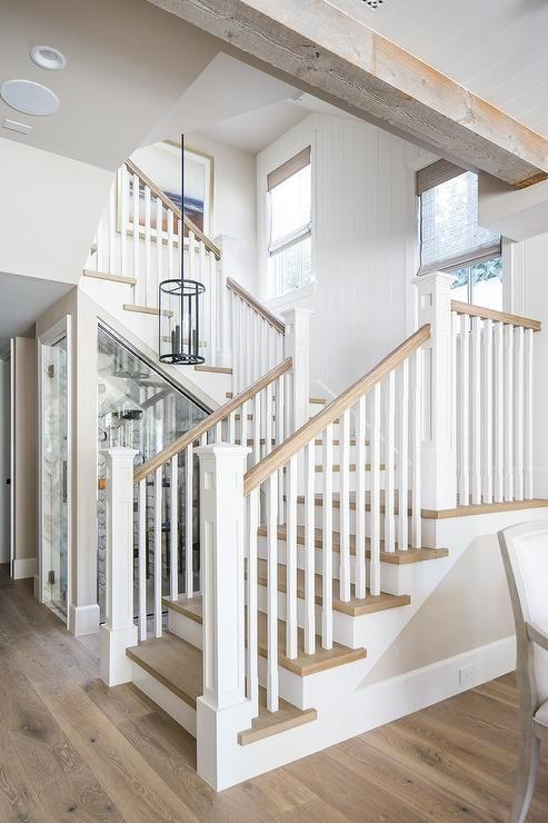 An Iron And Glass Pendants Hangs Over A Two Tone Staircase Fitted With Gray Wash Wood Treads Mat Beach House Interior Beach House Design California Beach House