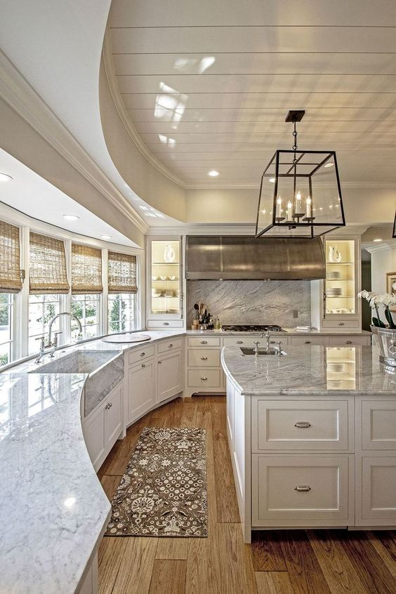 Luxury is definitely present here with the white marble countertops and large farmhouse sink (also marble). You can also see the wide spaces, large island and marble backsplash over the large stove.