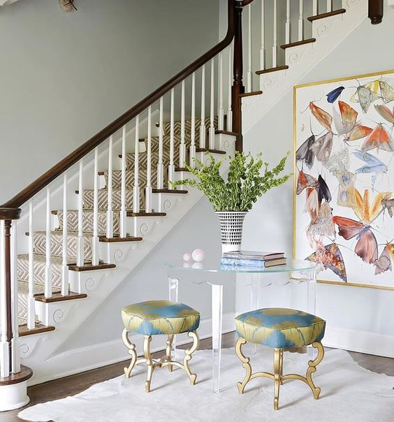 Staircase and entry with modern butterfly art and acrylic table with stools. Rachel Halvorson Inspired Decorating Tips. #staircase #interiordesign #modernart