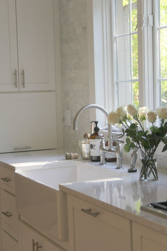 Modern farmhouse kitchen decor in this white classic kitchen with Shaker cabinets, fireclay farm sink, and marble subway tile, Viatera quartz countertop in Minuet and stainless bridge faucet. Design by Hello Lovely Studio. #whitekitchen #modernfarmhouse #farmsink #kitchendecor #whitedecor #serene #frenchcountry
