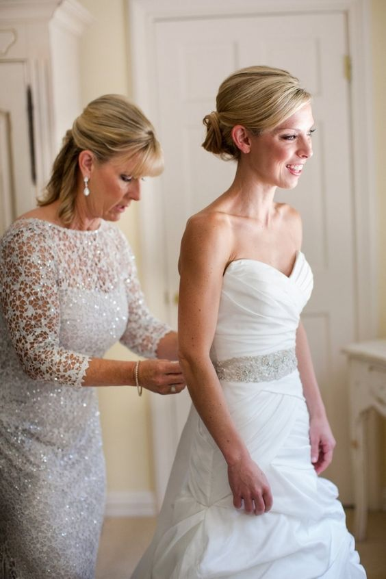 Lovely photo of the bride getting ready with her mother