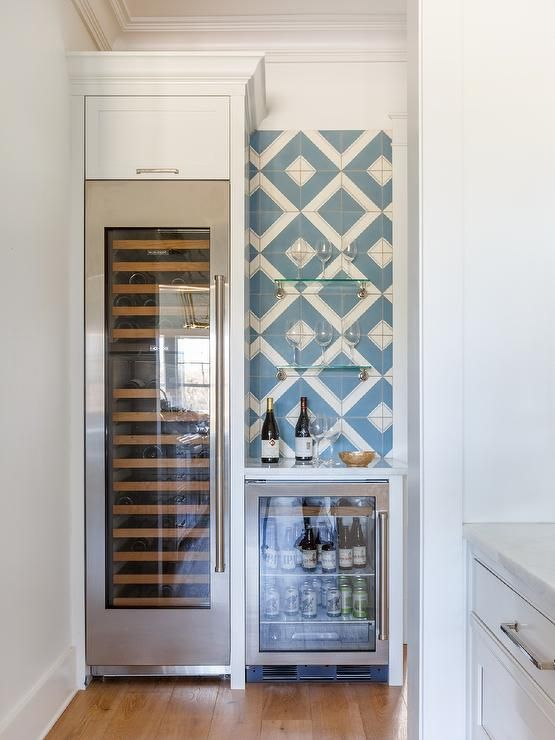 A Glass Front Wine Fridge Is Fitted Beneath A White Cabinet And Beside A Beverage F Built In Wine Refrigerator Beach House Interior Beach House Interior Design