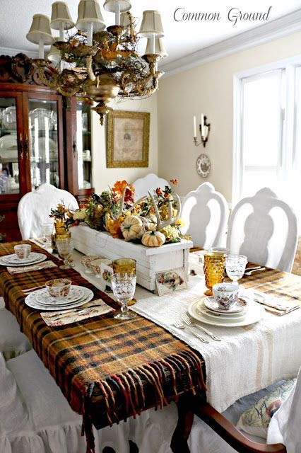 Nature Inspired Thanksgiving Tablescape by Common Ground - White flower box used as center piece, filled with leaves, antlers, pumpkins, vines and berries; brown plaid wool blanket for a tablecloth; grain sack runner; mixture of brown transferware and ironstone dishes; vintage Thanksgiving cards in old flower frogs for place cards; white, ruffled chair covers.