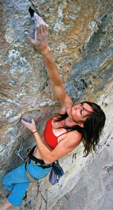 a photo of a woman hanging off a rock face as she is climbing it