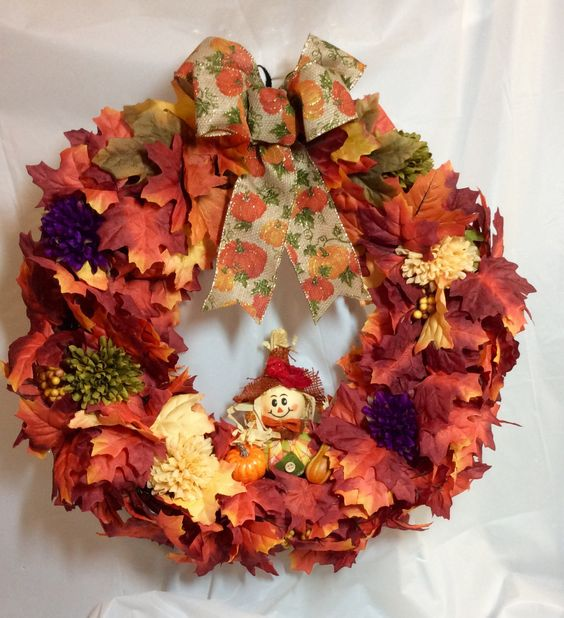 """Fall scarecrow wreath. Orange yellow maple leaves, fall mums on 18"""" vine form. Stuffed scarecrow. Pumpkin print bow. Faux flowers, leaves. by KhQualityCreations on Etsy"""