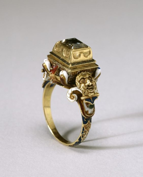 16th century European. Gold, enamel, diamond. This elaborate ring is set with a table-cut diamond in a raised box bezel supported by a structure resembling an inverted pyramid. The ring is lavishly covered with multicolor enameling extending on to the hoop. On each openwork shoulder, a large, grotesque mask is flanked by two enameled volutes.:
