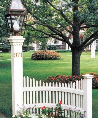 "Oyster Bay Accent - A stylish and dignified entrance to highlight your driveway or perhaps to accent a path. This decorative fence section consists of a 3' radius curve with stepped scalloped pickets dipping from 3 1/2' to 3'. Facias, backing rail and a 5"" sq. post with Colonial cap complete this accent. You choose a pillar post and lantern, sold separately. Shown here with a Belmont Pillar Post and a Beacon Lantern (22). Crafted from cellular vinyl, a wood-alternative and prefinished"