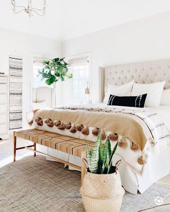 neutral color scheme // boho bedroom design // cream tufted headboard // woven bench