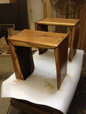 Two side tables made from slab wood, the first cut of a log containing the bark