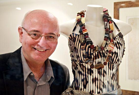 Alberto Sabino mostra seus colares de resina.