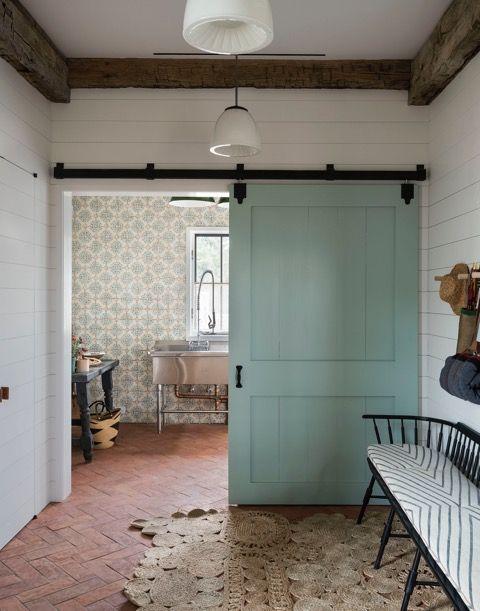 Beautiful modern farmhouse by Jennifer Bunsa with sliding Shaker style barn door, shiplap, rustic wood beams, herringbone tile floor, and industrial freestanding stainless sink. #modernfarmhouse #barndoor #mudroom
