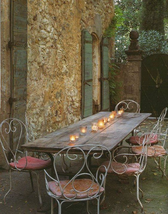 Beautiful French Country outdoor dining with rustic table lined with votive candles and iron armchairs.Romantic French Country Garden Courtyard Ideas. #frenchcountry #provence #courtyard #dining #rustic
