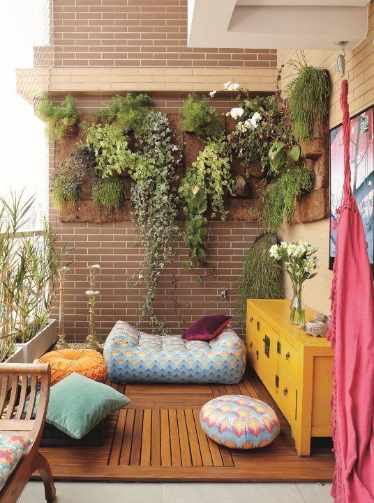 Um deck só no canto da varanda, com muitos pufes, almofadas e, é claro, a parede verde::