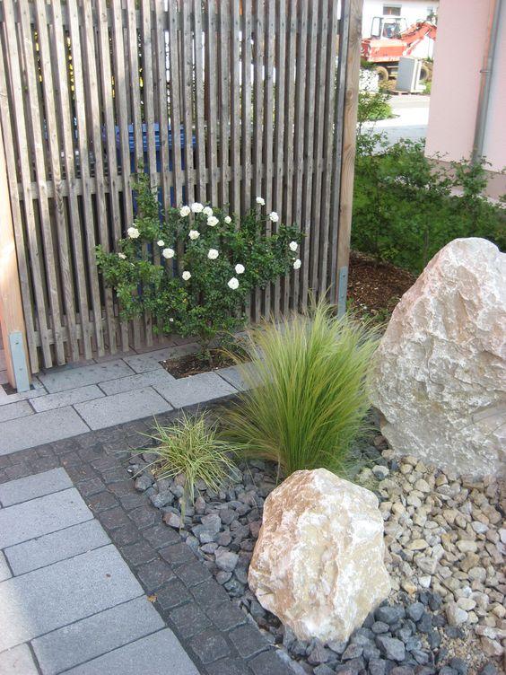Pflegeleichtes Steinbeet mit Kalksteinfindlingen. Bepflanzung mit ...