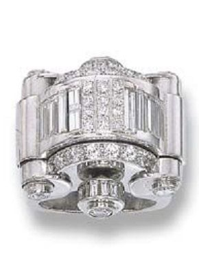 AN ART DECO DIAMOND WATCH RING, BY BAUME & MERCIER. The baguette-cut diamond domed top with diamond scroll sides opening to reveal the rectangular cream dial with baton markers, lever movement, circa 1935, with French assay mark for platinum Dial and movement signed Baume & Mercier. #BaumeMercier #ArtDeco #watch #ring