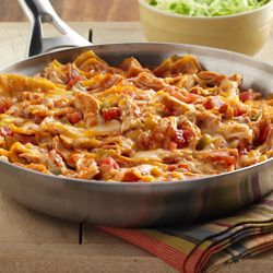 The flavor of enchiladas in a quick skillet presentation made with torn corn tortillas and cooked chicken tossed in a spicy enchilada sauce with cheese