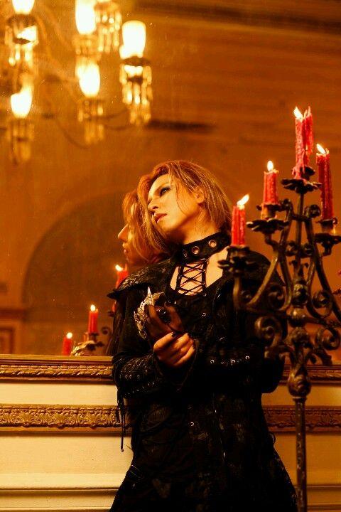 鏡の前で赤い蝋燭の横に立っているXJAPAN・YOSHIKIの画像