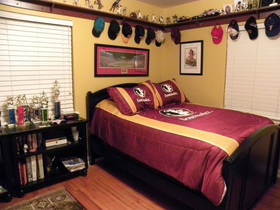 "Teenage Sons ""Man Cave"", I was really reluctant when my son wanted to change his decor to a sports theme. My fears were confirmed when he picked out his bedding! However, by the time we put it all together I think it has a sort of a den feel., My son has several collections and  the shelf around the whole room provides plenty of display space. , Boys Rooms Design"