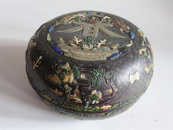 [Adjugé] 46 000 euros par Boisseau Pomez à Troyes le 27 septembre 2014  CHINE-XVIII's. : Boite en zitan de forme ronde à décor incrusté de nacre, ivoire teinté, turquoises, malachite, stéatite et fils d'argent du caractère ''chun'' (printemps) contenant un médaillon orné de Shoulao entouré de deux dragons pourchassant la perle sacrée, au-dessus d'un panier chargé d'objets précieux, les bords ornés de lettrés et leurs serviteurs dans un paysage sur fond de croisillons et fleurettes.