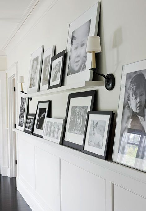 Family portraits line the shelves in this hallway. Photo: John Granen