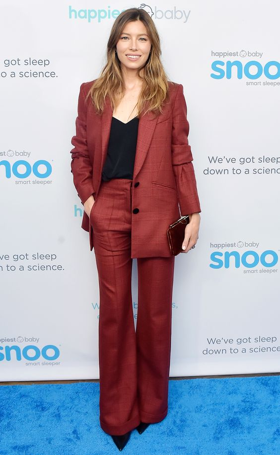 wears a red pantsuit, black top, small clutch and pointy-toe pumps at Jessica Biel and Dr. Harvey Karp Celebrate Moms, Dads and their Favorite Helper, the SNOO, in West Hollywood.