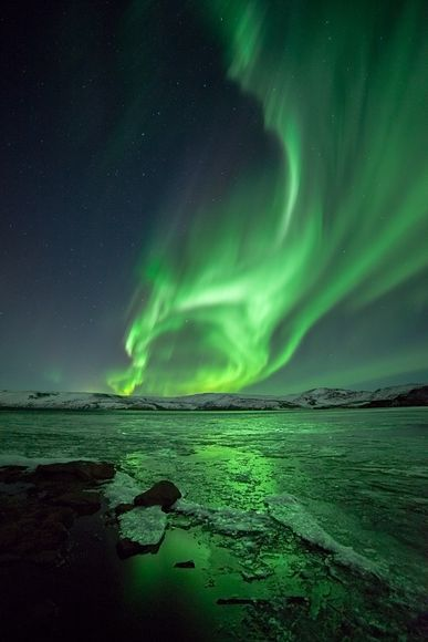 A picture of an aurora borealis over the frozen lake Kleifarvatn in Iceland: