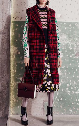 Rendered in a dimensional plaid wool, this **Marni** vest features a collarless design with oversized buttons at the bodice and a long boxy silhouette with raw edge details.