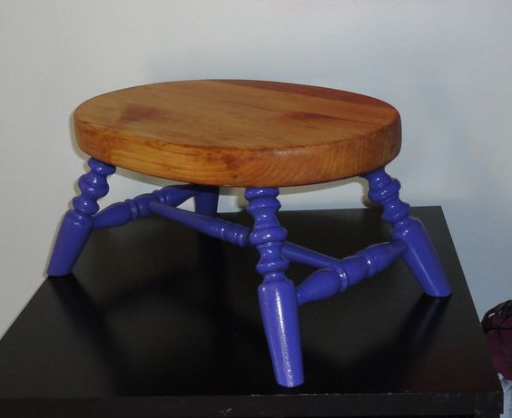 Foot Stool - Hidden Gem Furniture -- This old stool was originally painted all black. Brought out the beauty of the natural wood underneath with a sander and some golden pecan stain to contrast the freshly coated purple legs.