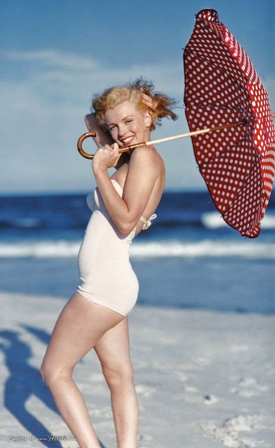 Marilyn Monroe in a white swimsuit at Tobay Beach with a polka dot umbrella, Long Island, Summer 1949.: