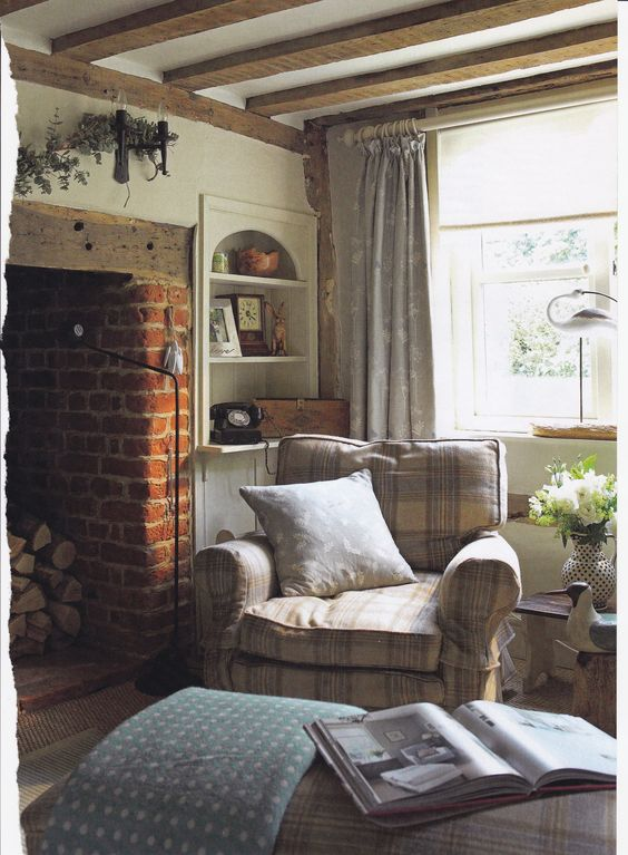 Cosy cottage living room. Checked armchair and footstool with throws. Brick inglenook fireplace and wooden beams.: