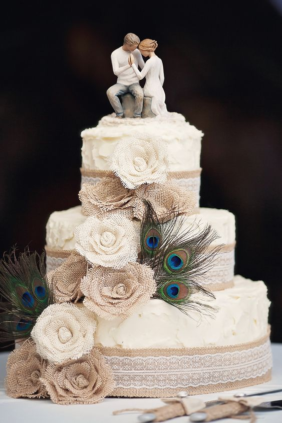 Cake: Burlap flowers, peacock feathers, burlap ribbon with lace, buttercream frosting, vanilla cake, chocolate mouse filling.: